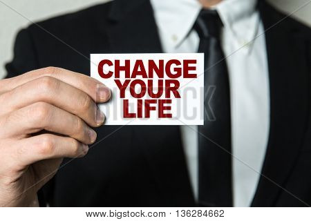 Business man holding a card with the text: Change Your Life