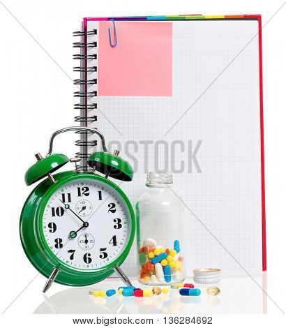 Medical concept - green alarm clock with pills, water and blank notebook,  isolated on white background