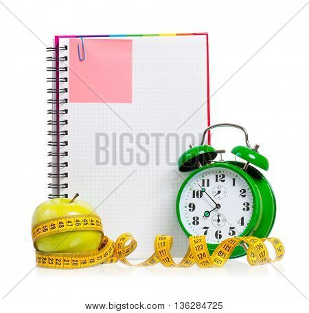 Concept of diet - alarm clock, apple, measuring tape and  blank notebook,  isolated on white background