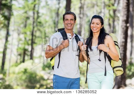 Couple smiling and posing with their backpack on the wood