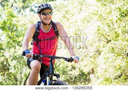 Mature man riding bike on the wood
