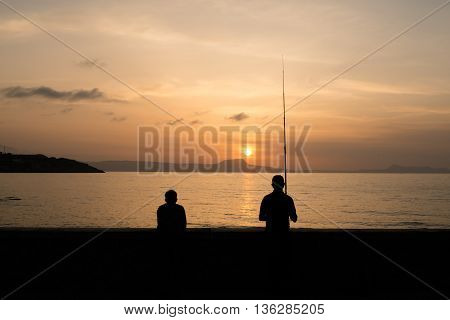 Greece, Rethimno - May, 19. 2016: Sundown At Rethimno With Two Fishers At The Boardwalk Wall.
