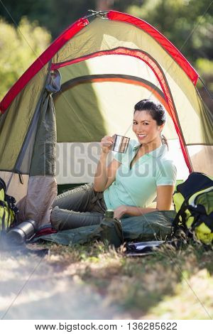 Woman sitting and holding a cup on a tent