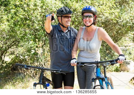 Couple smiling with their bike on the wood