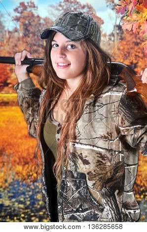Close-up of a pretty teen girl in camouflage walking by wetlands to an autumn woods with her rifle across her shoulders.