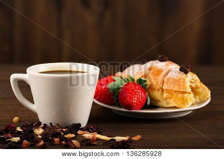 A cup of black tea with dry fruits croissant with strawberry and wooden table background