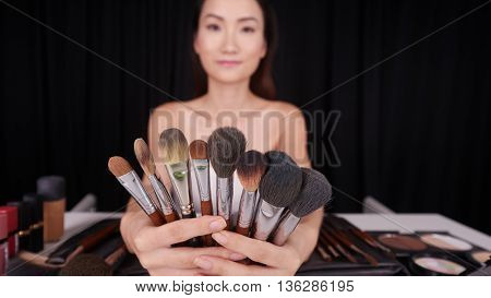Young woman showing set of her make-up brushes, selective focus