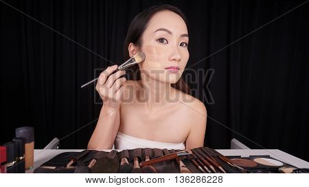 Asian young woman applying foundation on her face