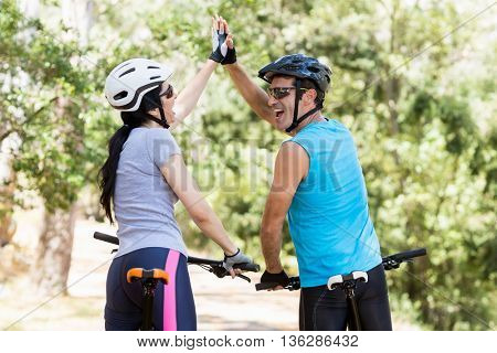 Couple from the back clapping hands each other on their bikes