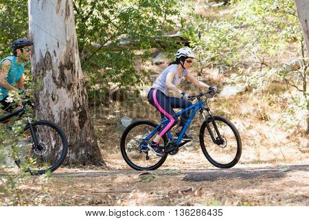 Profile view of Couple riding bike in the wood