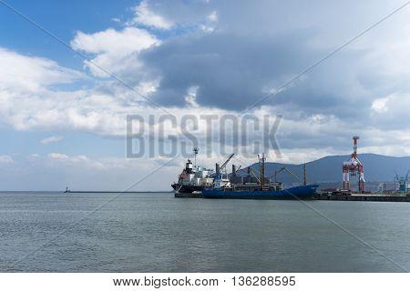 cargo ship parks against dock in hokkaido in cloud sky