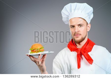 Male chef cook with delicious burger on a plate. Fast food.