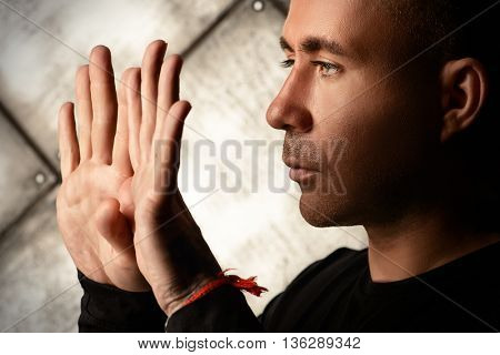 Yoga concept. Mature man in black clothes doing yoga exercises and meditation over dark background.