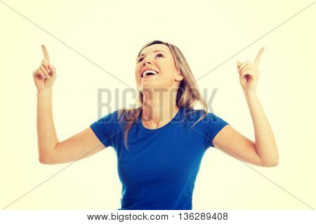 Young casual woman pointing up.