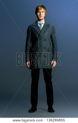Fashion shot of a handsome man in an elegant coat. Beauty, fashion. Studio shot.