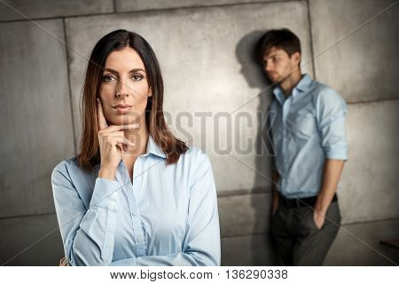 Portrait of serious businesswoman, businessman standing at background.