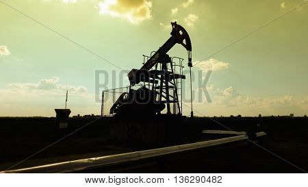 Pump jack and wellhead silhouette, Extraction of oil