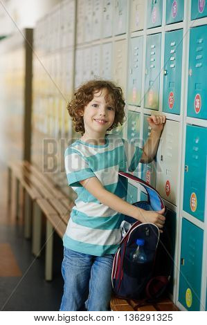 The primary school students standing in the hall near the lockers. The boy opened the backpack and something shifts.He has a pretty face and curly blond hair.