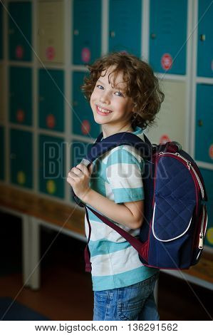 Elementary school student standing near lockers in school hallway. Behind kid's school backpack. The boy has blond curly hair and blue eyes. HE smiles.