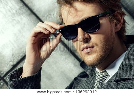 Portrait of a handsome young man in sunglasases. Beauty, fashion. Studio shot.
