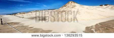 Panoramic image of sand dunes and blue sky.