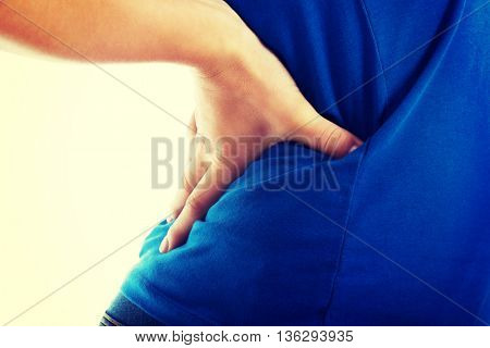 Casual woman is having a back pain. Close up.
