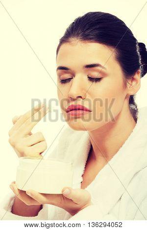 Beautiful woman in bathrobe with face cream.