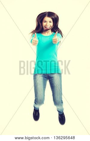 Young casual woman jumping and showing OK.