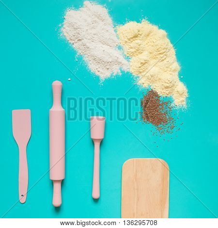 Kitchen utensils baking accessories pink rolling pin spatula and flour with spices on a turquoise background.