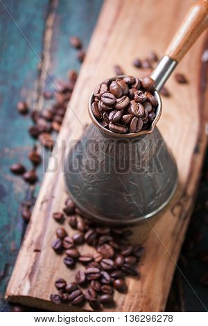 Roasted coffee beans in a cooper turk on a vintage background closeup