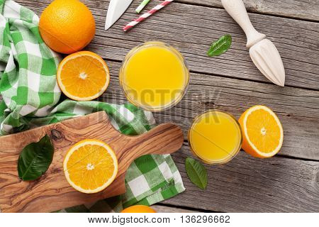 Fresh ripe oranges and juice on wooden table. Top view