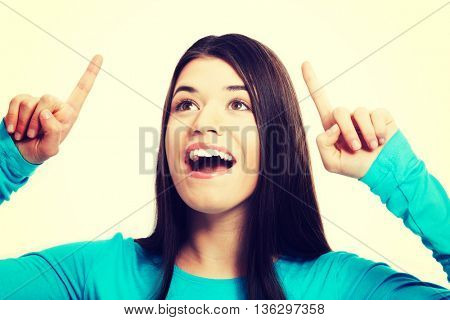 Portrait of a casual woman pointing up.