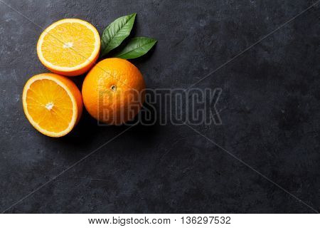Fresh ripe oranges on dark stone background. Top view with copy space