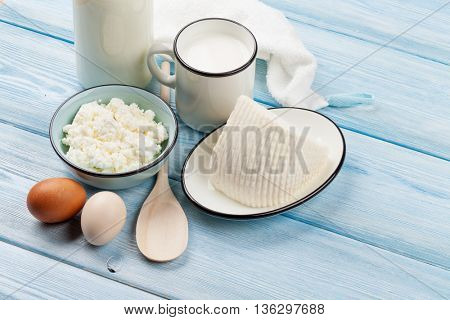 Dairy products on wooden table. Sour cream, milk, cheese, eggs and yogurt