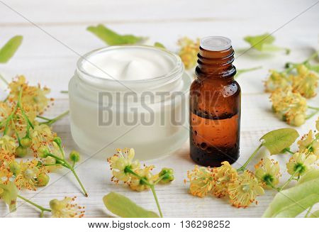 Jar of white cosmetic facial cream, essential oil bottle, linden (tilia) blossom flowers. Holistic herbal skincare.