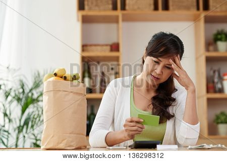 Unhappy mature housewife looking at credit card after shopping