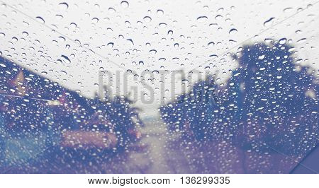 raindrops on car windshield running on road
