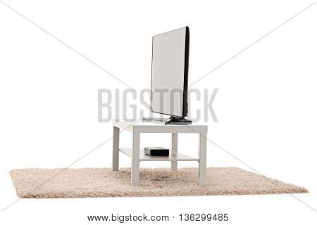 Studio shot of a big flat screen TV white table isolated on white background