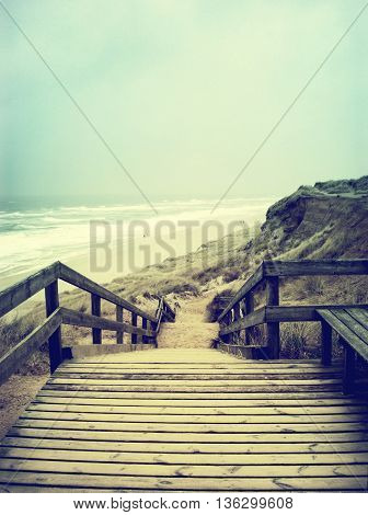 Lonely footpath or wooden stairway through a beach dune. Beach on Sylt with stormy sky