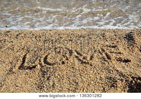 Word LOVE written on golden beach sand