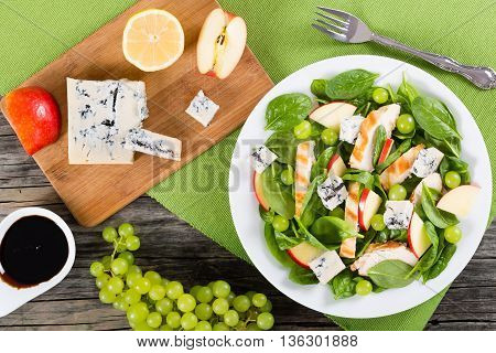 grilled chicken breast grapes spinach cheese and apple salad on a white dish on a table mat cutting board with pieces of apple lemon and blue cheese view from above