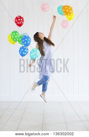 Happy young teen girl with helium air balloons. Holidays and happiness concept