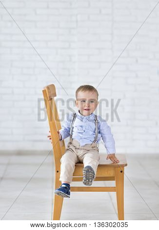Beautiful adorable laughing baby boy sitting on the chair. Smiling blue-eyed child sits on a chair
