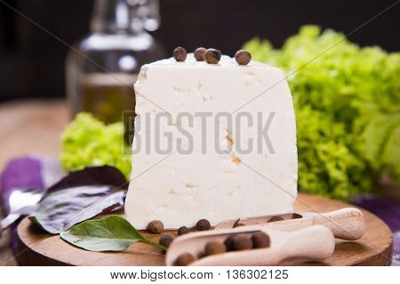white fresh cheese with lettuce,basil and pepper on wooden plate