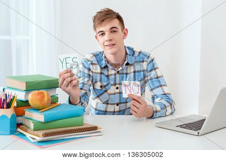 Modern problem: youth and computers. Young student using laptop and looking at camera. Guy holding sticker with words yes and no. Nice white interior with table full of books