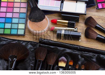 Set of professional make up brushes, lipsticks, maskara, eye shadows and powder on desktop, top view