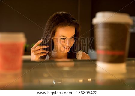 Portrait of a beautiful young woman taking away a cup of coffee at the bar in a coffee shop