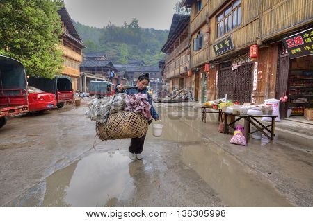Zhaoxing Dong Village Guizhou China - April 8 2010: Street tradeswoman with a yoke on his shoulder carries a large wicker cage on street settlements of ethnic minorities passed wooden houses.