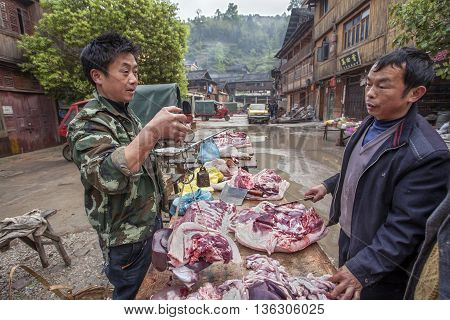 Zhaoxing Dong Village Guizhou Province China - April 8 2010: Asian butcher weighing pork for a buyer using Chinese scales.