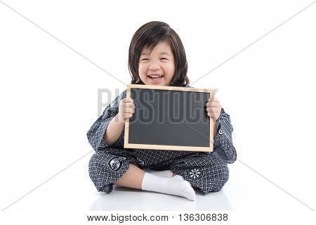 Cute asian boy in kimono holding black board on white background isolated